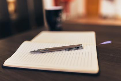image of open notebook with pen